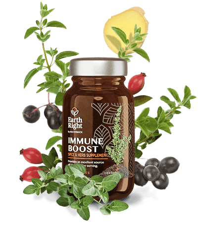 Immune Boost supplement in sustainable glass bottle surrounded by acerola cherry, garlic, oregano, black elderberry, and other wellness herbs and spices