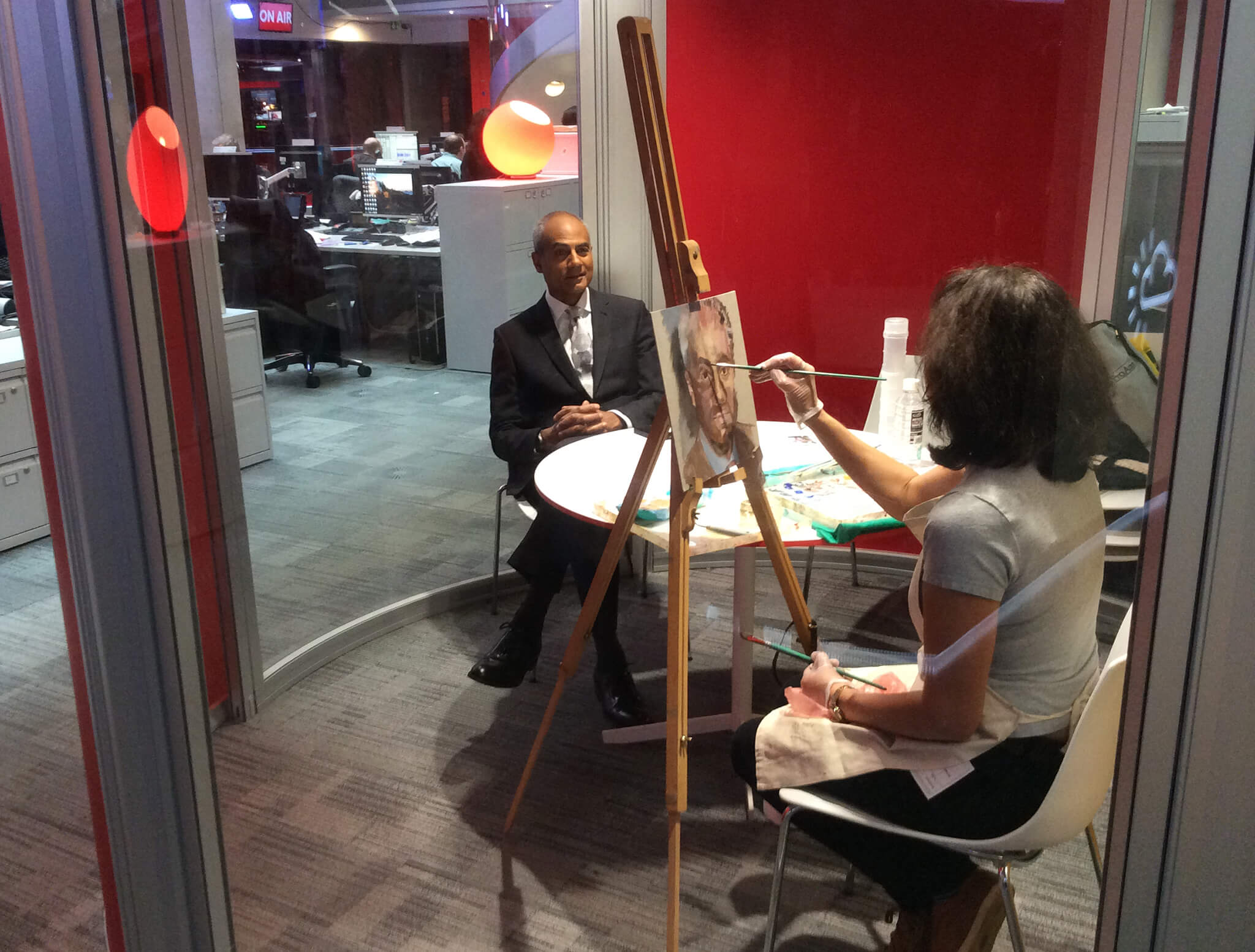 Artist Stella Tooth painting oil study on canvas board of BBC's George Alagiah in the BBC Newsroom.