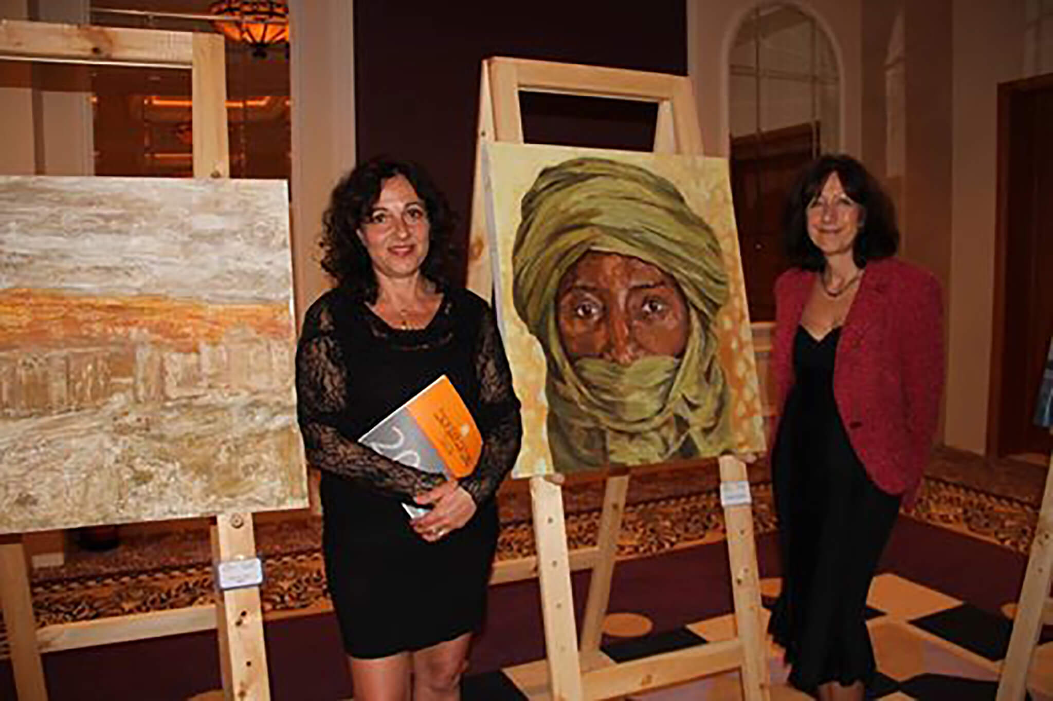 Artist Stella Tooth with her Saharan Tuareg portrait at Egypt's first art biennale in Sharm El Sheikh.