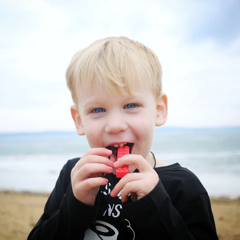 Caucasian toddler chewing on Ark's brick stick textured sensory chew necklace in red