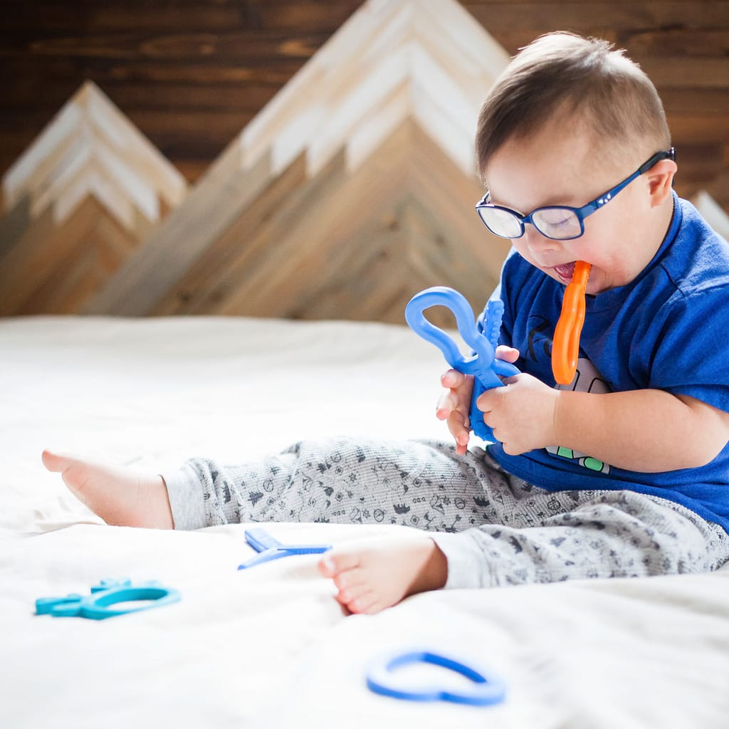 Autistic toddler wearing glasses chewing on Ark's guitar chew fidget