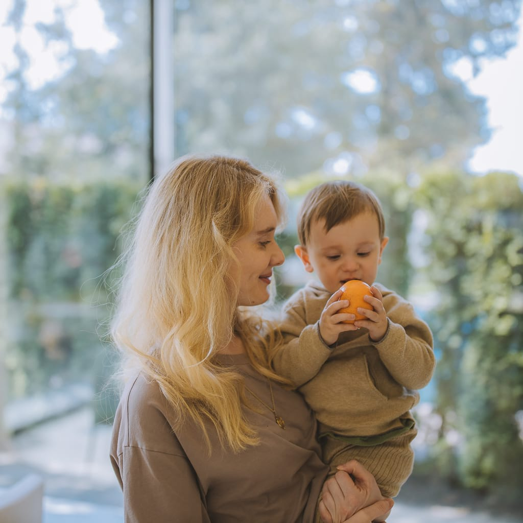 Sensory Stand owner holding her toddle son who is eating an orange