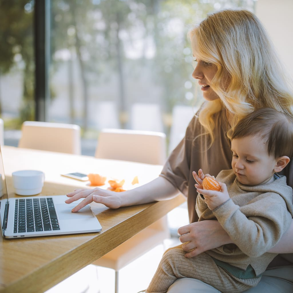 Owner of Sensory Stand working on the computer while holding her son
