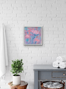 Painting in soft corals and teals with white frame against a white brick wall in a bathroom.