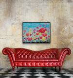 Load image into Gallery viewer, Vibrant art shown above a red leather sofa against a natural brick wall