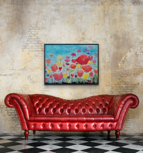 Vibrant art shown above a red leather sofa against a natural brick wall