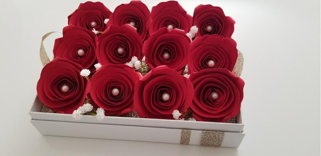 A full view of the one dozen red, paper roses sitting atop the removable tray inside the box.