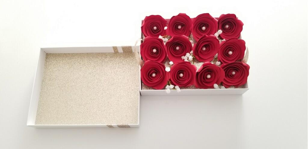A full view of the one dozen red, paper roses sitting atop the removable tray inside the box; pictured with the inside of the lid.