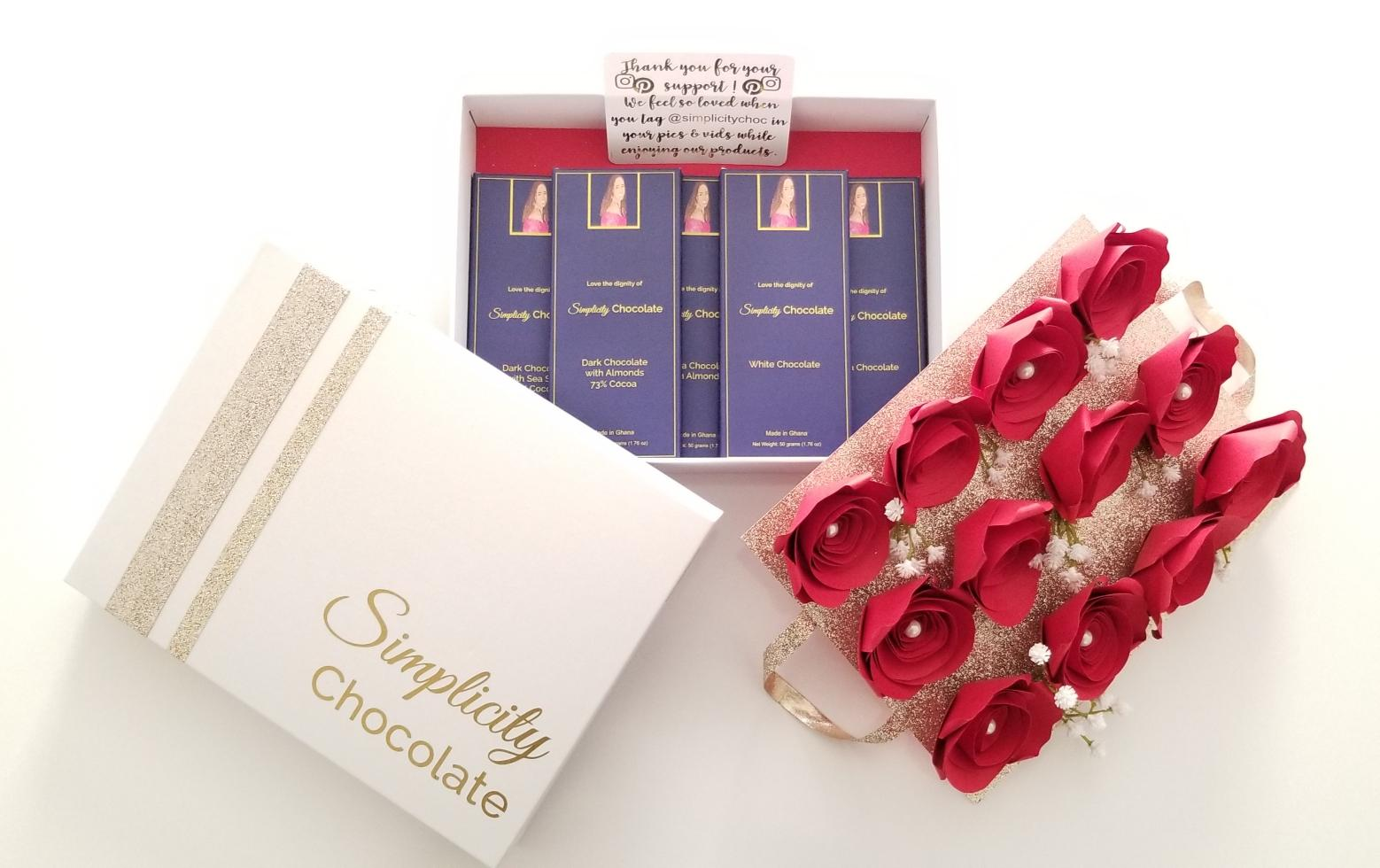 The Simplicity Chocolate Nostalgia Box is seen here as a white box with gold accents. The Simplicity Chocolate signature logo adorns the lid in gold print. A layer of one dozen red, paper roses sits atop a gold platform with handles that when lifted reveal the five gourmet Simplicity Chocolate flavor offerings nestled in the keepsake storage portion of the box.