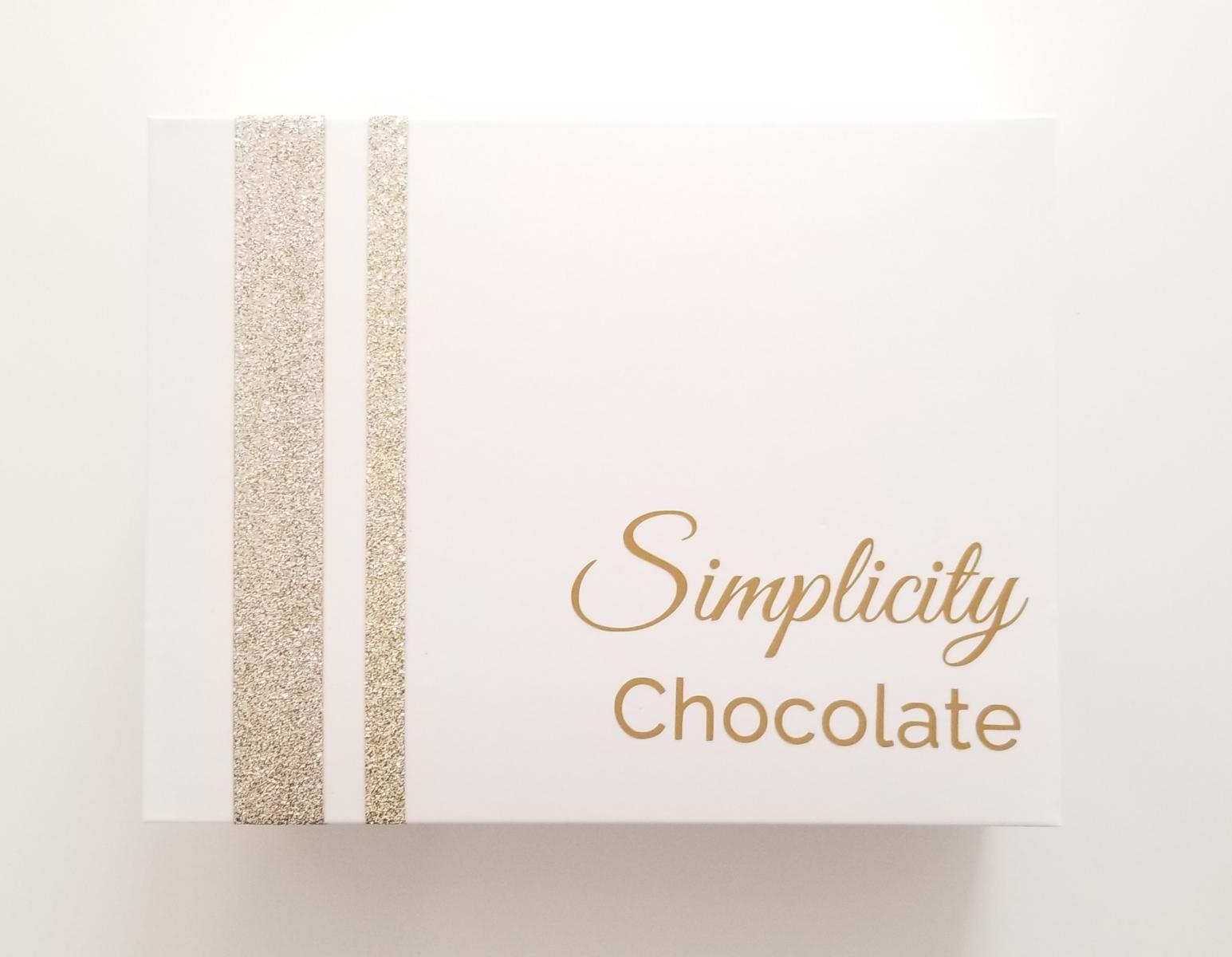 The lid of The Simplicity Chocolate Nostalgia Box with gold accents and the signature logo in gold writing.