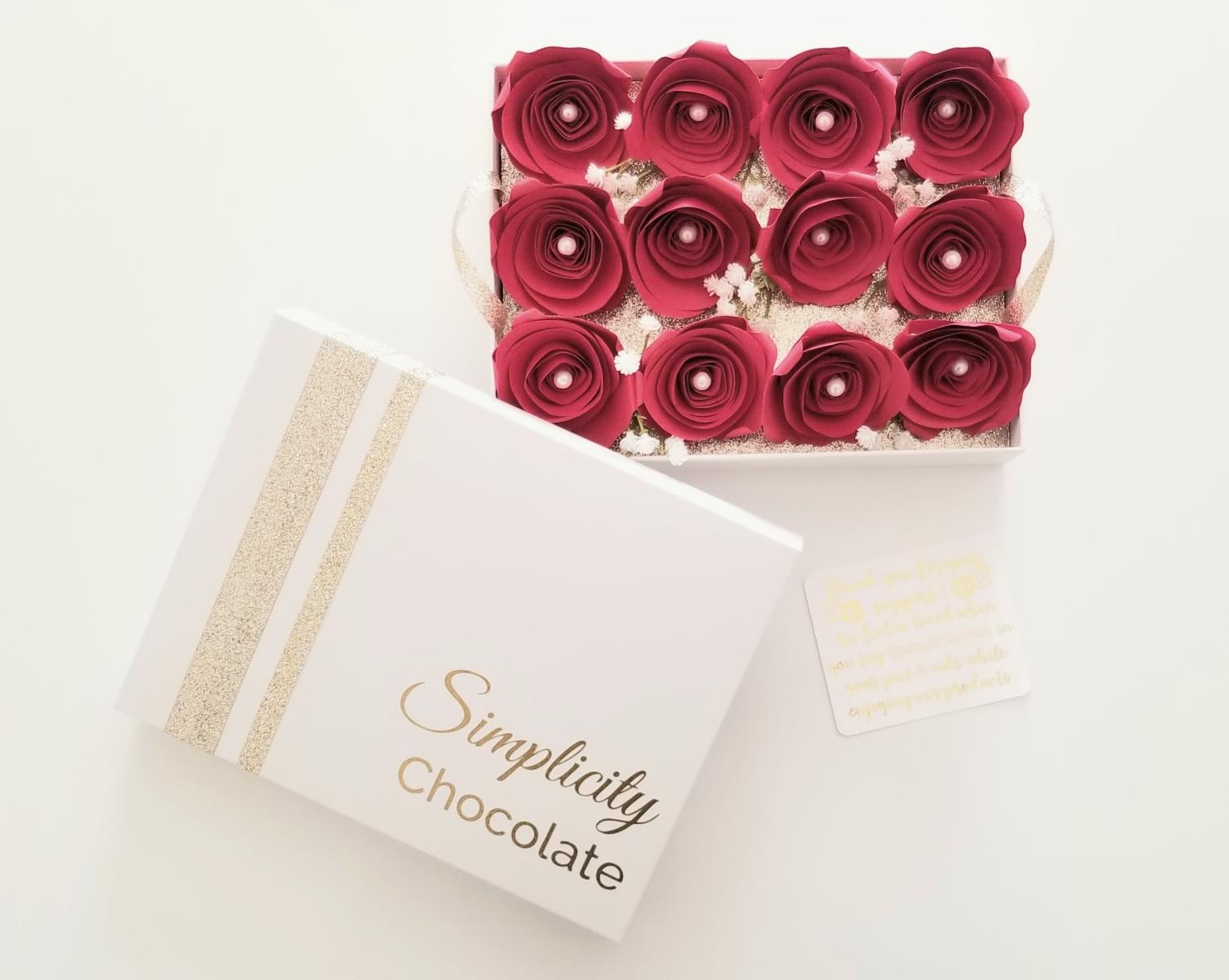 The lid of The Simplicity Chocolate Nostalgia Box with gold accents and the signature logo in gold writing is pictured next to a full view of the one dozen red, paper roses sitting atop the removable tray inside the box.