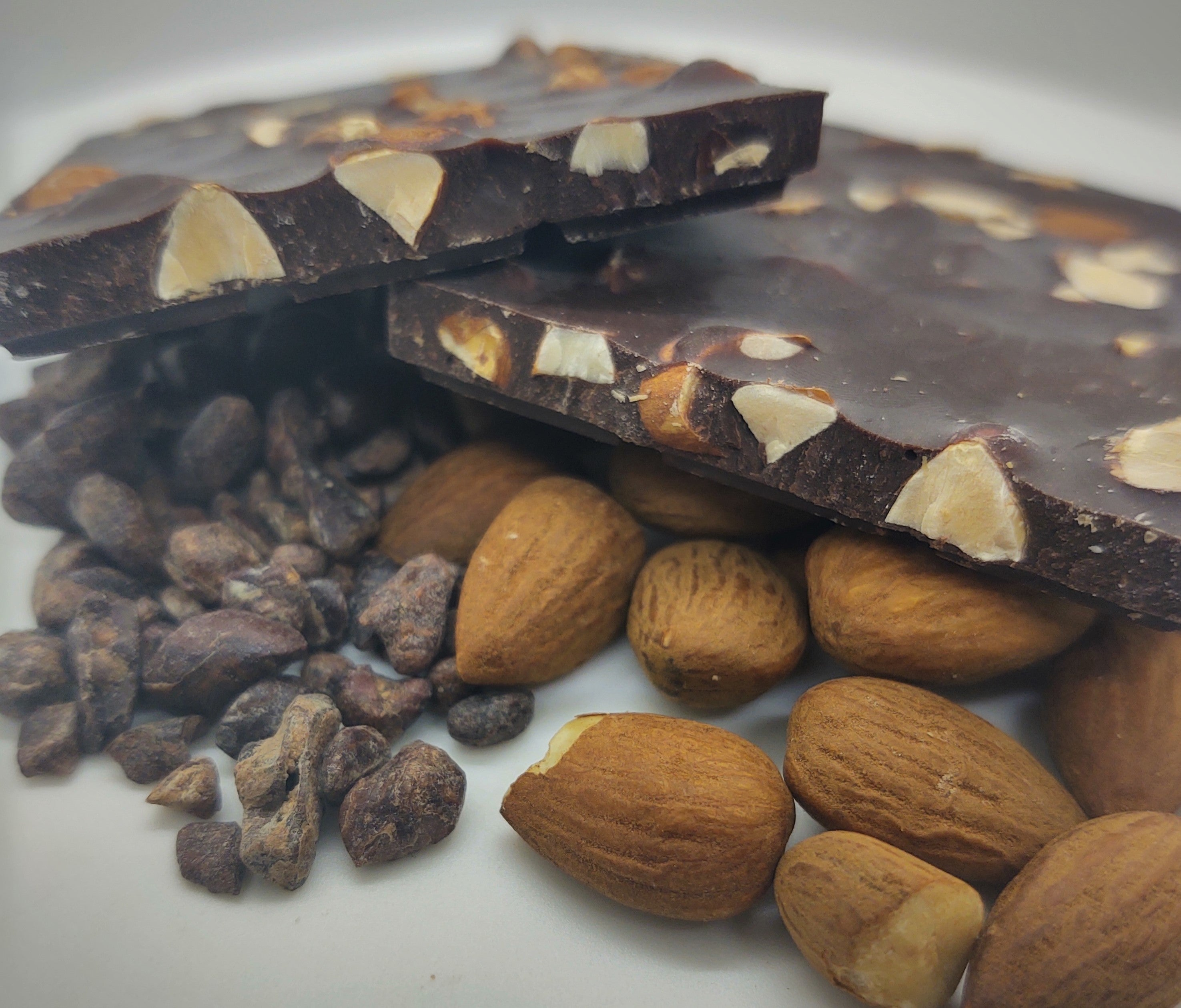 Pictured: solid dark chocolate bar with almonds. The bar is mounted by cocoa nibs and whole, roasted almonds