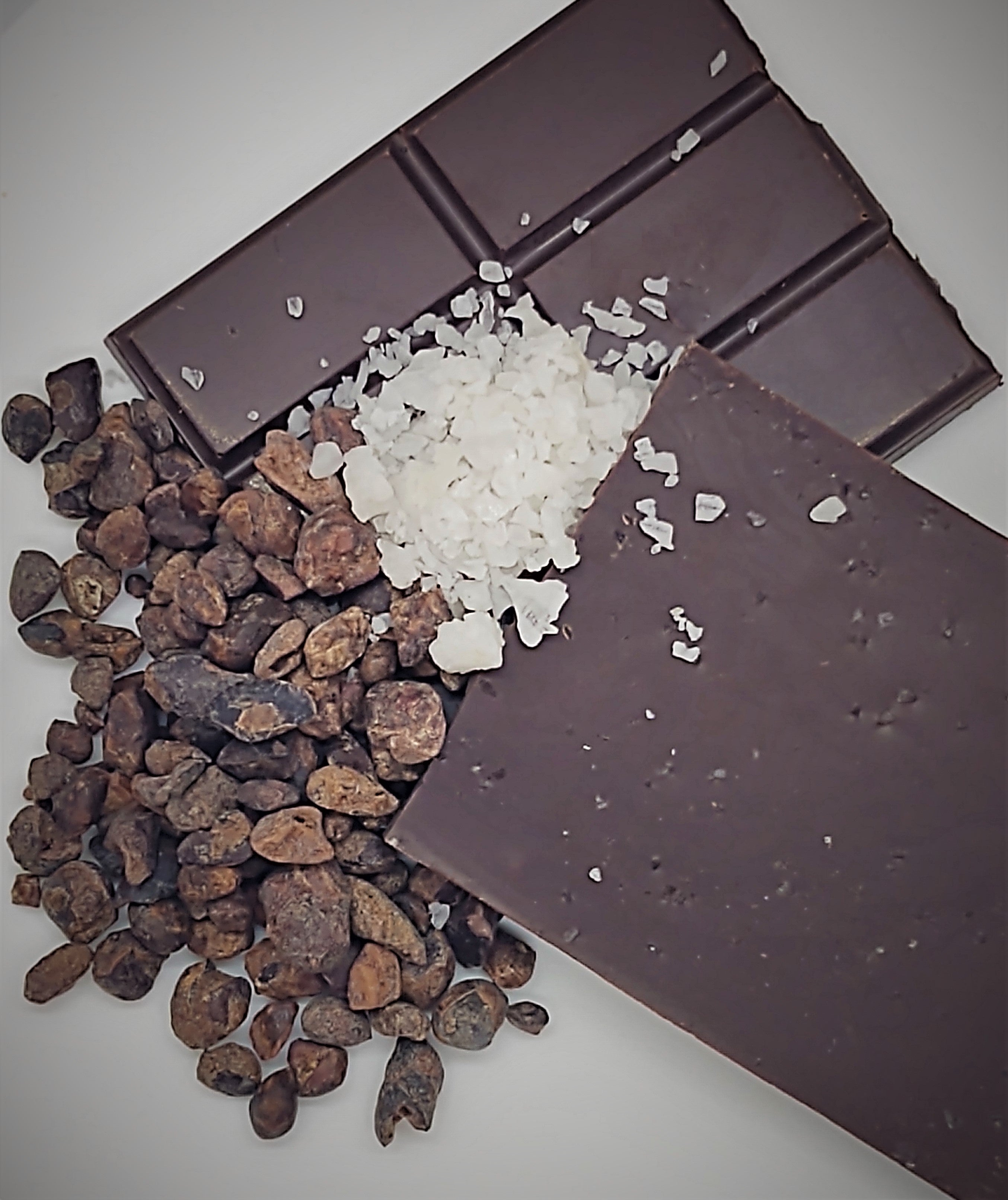 Pictured: Solid dark chocolate bar mounted by raw sea salt and cocoa nibs
