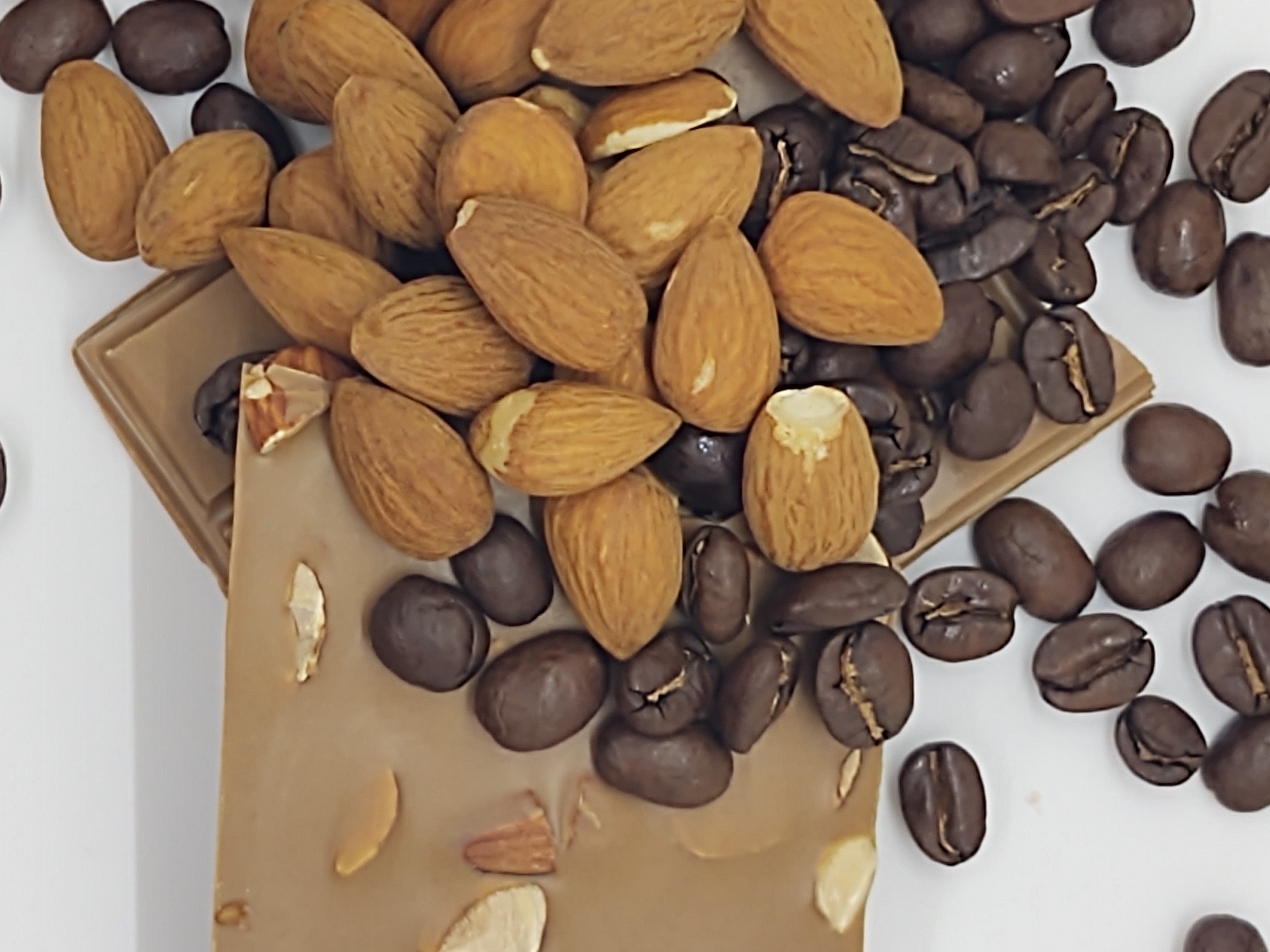 Pictured: a solid mocha flavored chocolate bar mounted by whole, roasted coffee beans and whole almonds