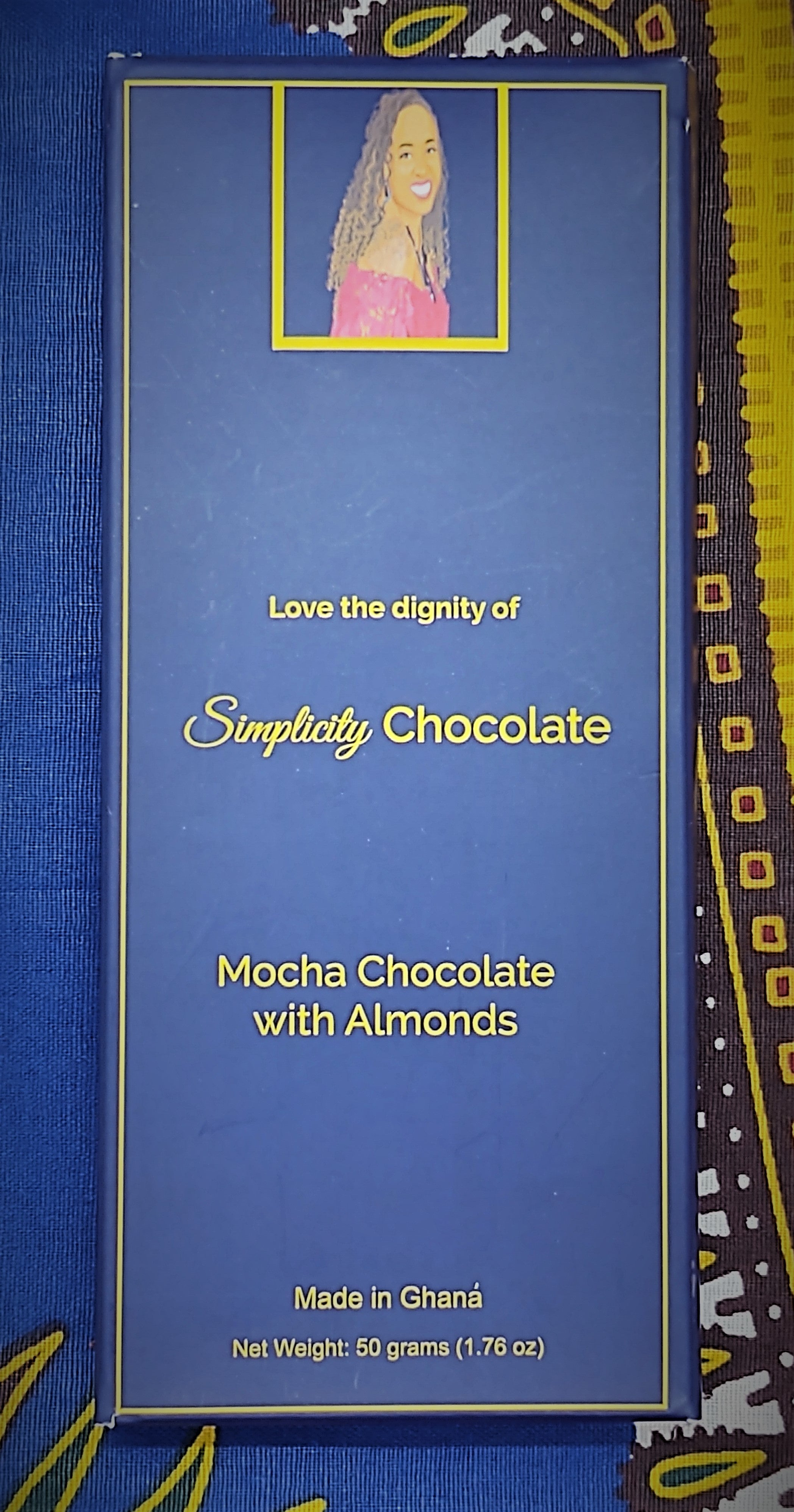 "Pictured: The Simplicity Chocolate bar wrapped in complete packaging which consists of a dark blue box with gold writing. A portrait of the CEO is centered at the top of the packaging. The CEO is seated, looking over her right shoulder, wearing a magenta, off the shoulder top and a royal blue gemstone necklace with matching earrings. The packaging reads, ""Love the dignity of Simplicity Chocolate"" in the center of the package. Mocha Chocolate with Almonds. Made in Ghana. Net Weight: 50 grams (1.76 oz)."