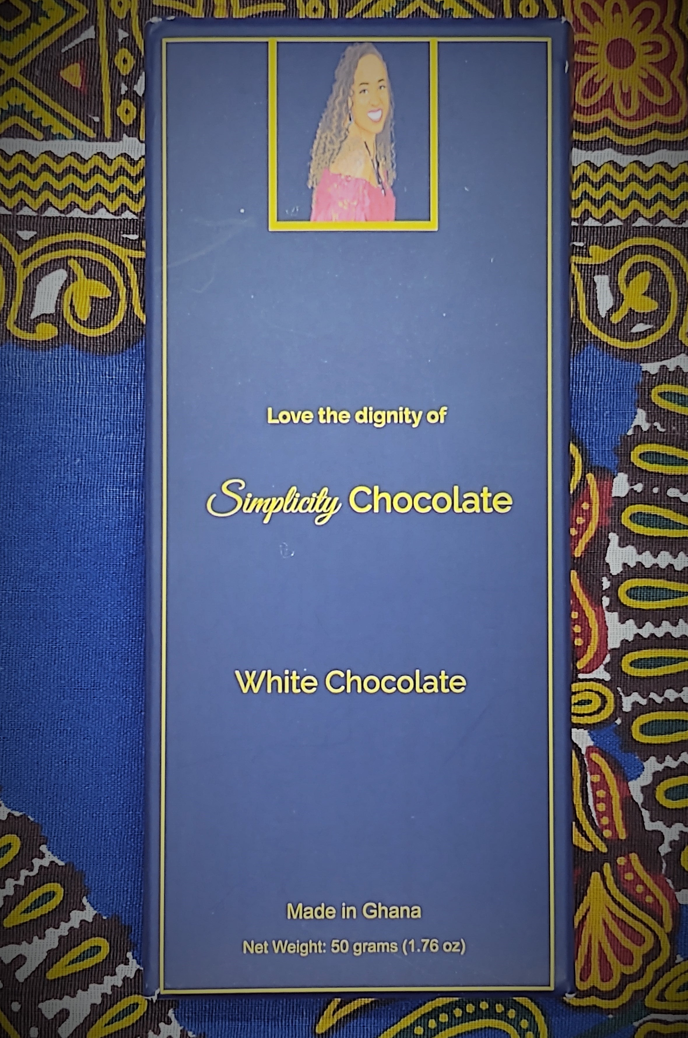 "Pictured: The Simplicity Chocolate bar wrapped in complete packaging which consists of a dark blue box with gold writing. A portrait of the CEO is centered at the top of the packaging. The CEO is seated, looking over her right shoulder, wearing a magenta, off the shoulder top and a royal blue gemstone necklace with matching earrings. The packaging reads, ""Love the dignity of Simplicity Chocolate"" in the center of the package. White Chocolate. Made in Ghana. Net Weight: 50 grams (1.76 oz)."