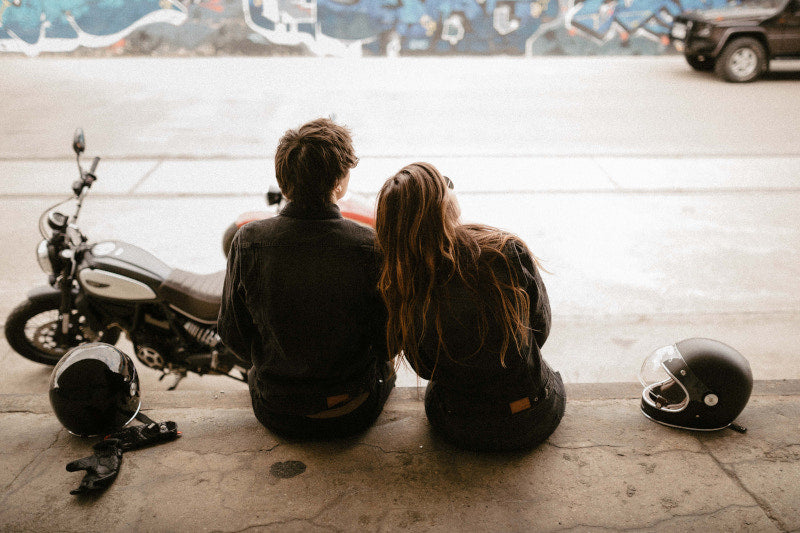 two people sitting on a wall, dressed in broger ohio appareal