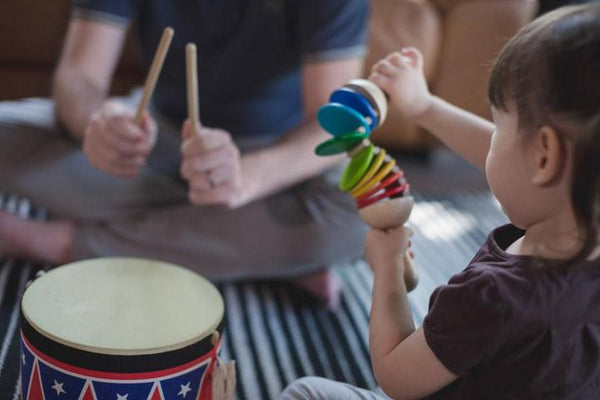 Babies playing with Plan Toys musical instruments