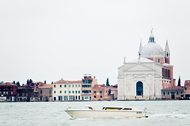 A boat cruises on a canal in Venice, the beautiful architecture of this city features  in the background
