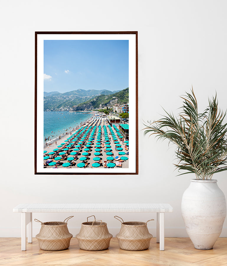 Beautiful print of the Amalfi beach in summer with rows and rows of its green umbrellas on the beach, with the blue sea and the green cliffs in the distance. Part of the Into The Blue series by Millie Brown