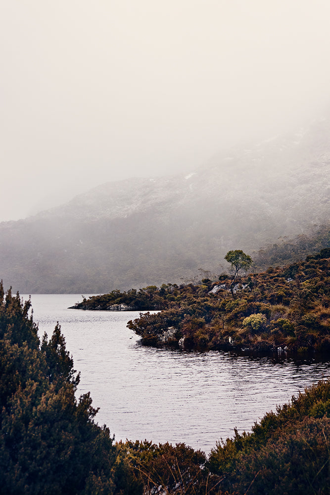 A corner of beautiful Dove Lake at Cradle Mountain in Tasmania, with its icy water and stunning wild bushland with Cradle Mountain shrouded in low cloud in the background