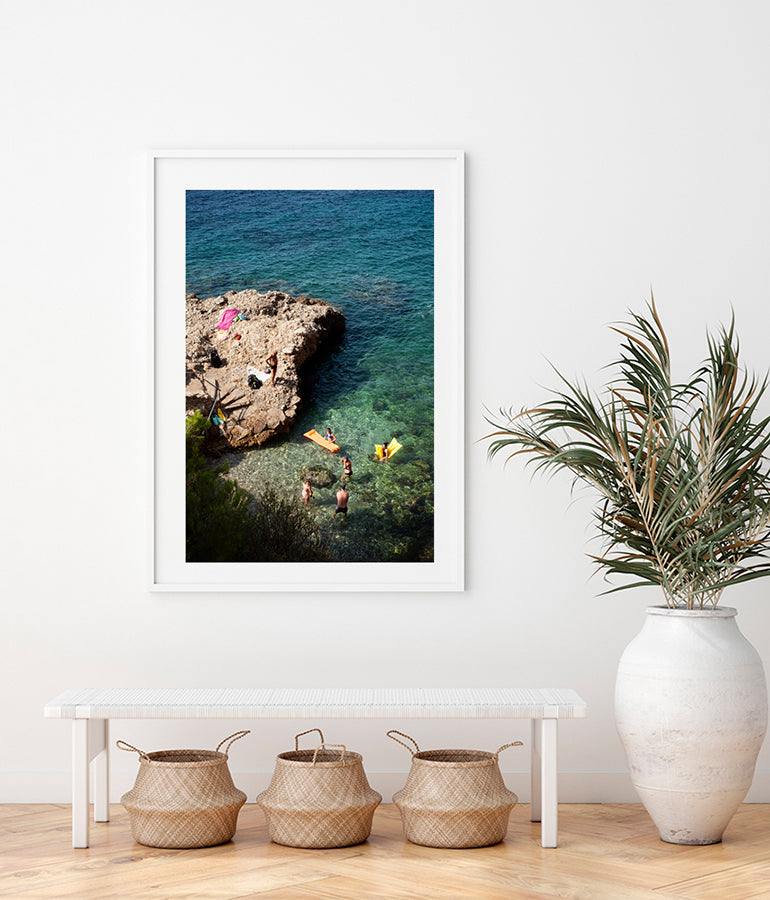 French Riviera print featuring people  in a beautiful swimming cove shot from above showing people swimming and standing with their colourful air mattresses on the water as well as on the rocks. Part of the Into The Blue fine art print series by Millie Brown