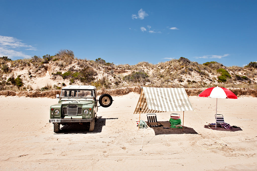 Photographic beach wall art print of long beach robe, featuring a land rover, beach umbrellas and chairs , with the beautiful sand dunes behind, available in small to extra large  artwork sizes, part of the Salty Days collection by Millie Brown