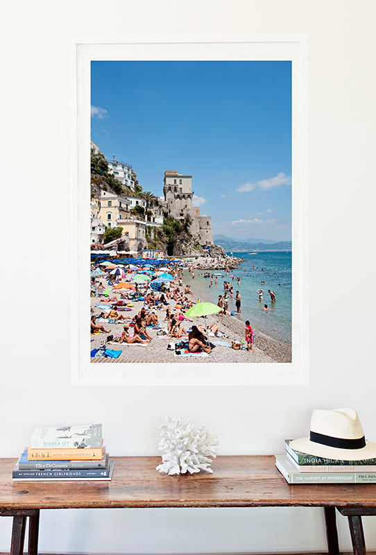 Amalfi coast photographic wall art print of Cetara beach on the Amalfi Coast with colourful beach umbrellas and beachgoers on the shore and in the sea and an old stone building in the background by photographer Millie Brown