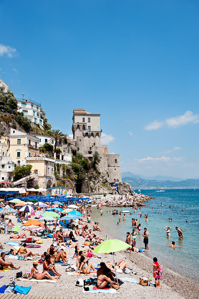 Amalfi coast photographic wall art print of Cetara beach on the Amalfi Coast with colourful beach umbrellas and beachgoers on the shore and in the sea by photographer Millie Brown