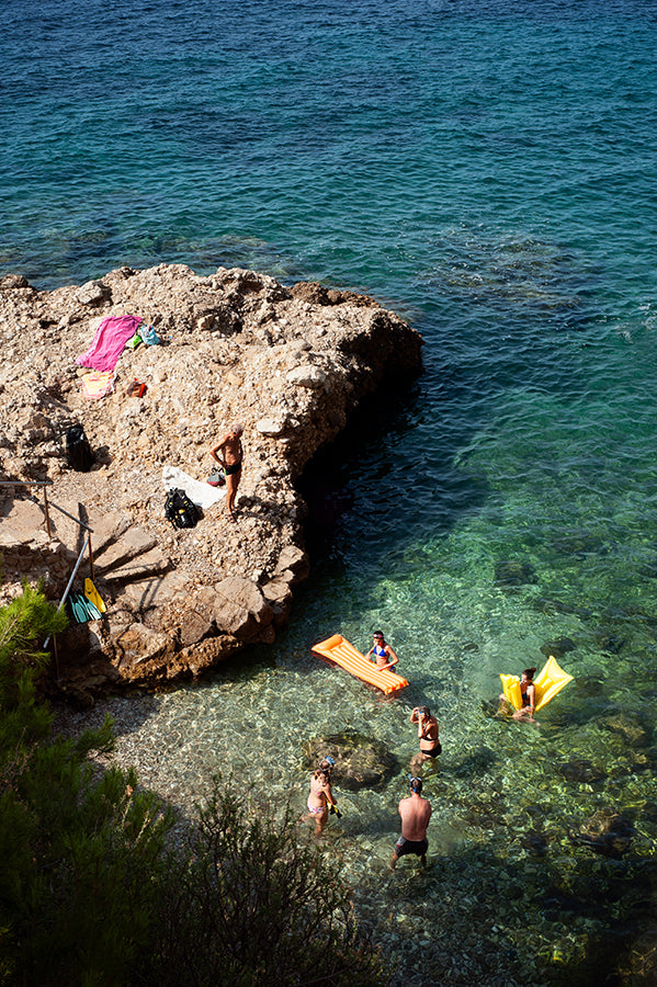 French Rivier swimming cove shot from above showing people swimming and standing with their colourful air mattresses on the water as well as on the rocks. Part of the Into The Blue fine art print series by Millie Brown