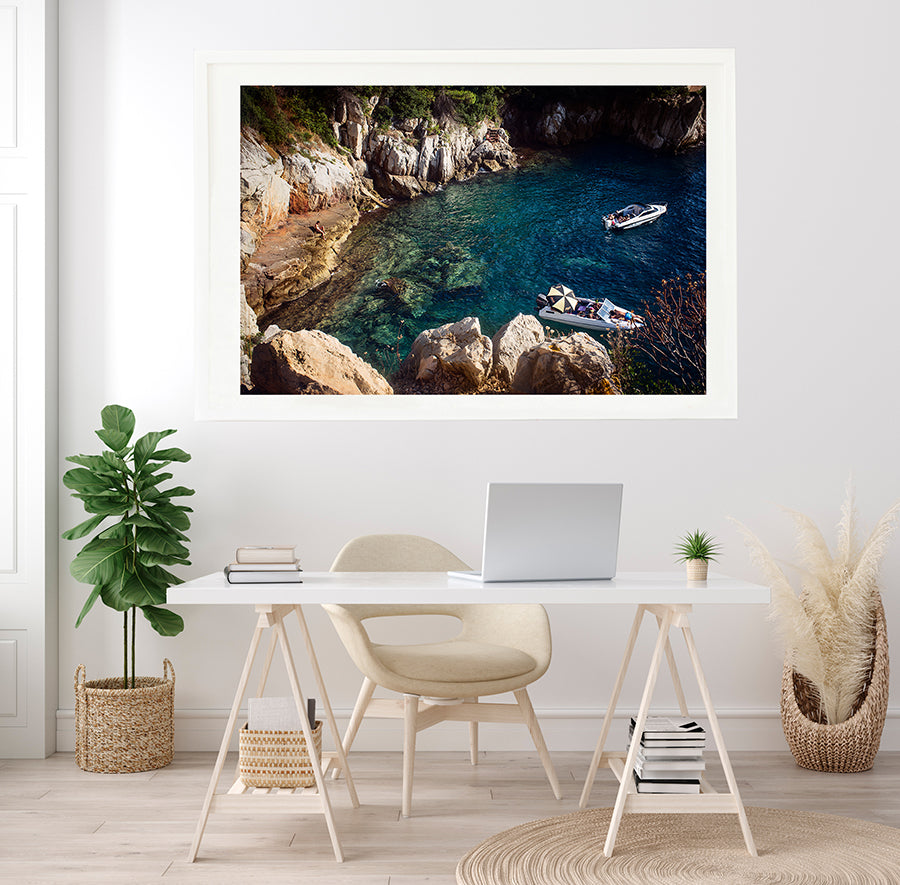 French Riviera Fine Art Wall print of summer in a Cap Ferrat swimming cove,  the blue mediterranean sea in a small cove on Cap Ferrat with a person sitting on the rocks and two leisure boats with people sun bathing by travel photographer Millie Brown