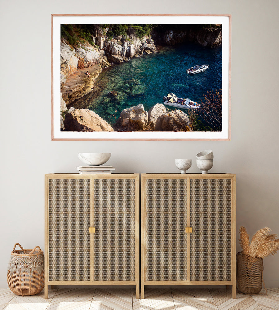 French Riviera Fine Art Wall print of the blue mediterranean sea in a small cove on Cap Ferrat with a person sitting on the rocks and two leisure boats with people sun bathing by travel photographer Millie Brown