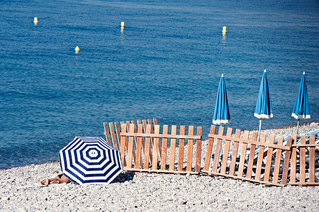 French Riviera Print featuring the pebbly beach in Nice France and a blue and blue beach umbrellas next to the blue mediterranean sea
