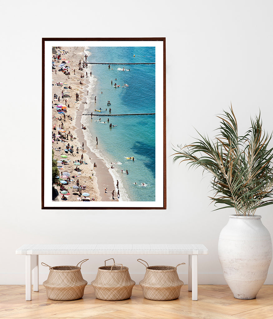 French Riviera beach wall art featuring the beach of Villefranche sur mer on a hot summer day with its colourful beach umbrellas and beach goers enjoying the sea and sun. Fine art prints by photographer Millie Brown