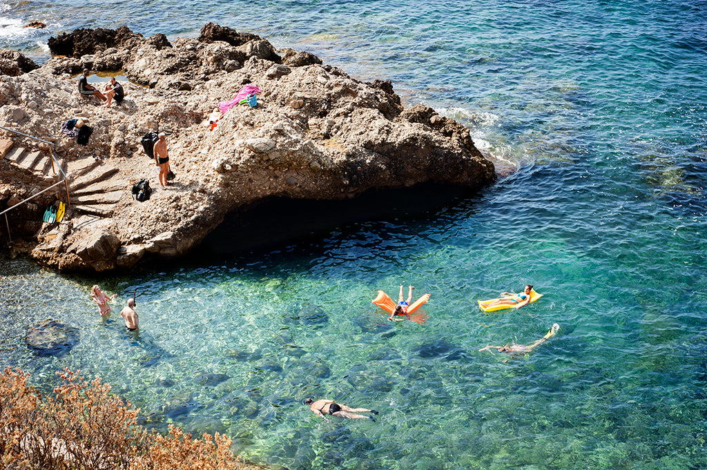 Cote d'azur wall art prints featuring the French Riviera and a small beautiful swimming cove surrounded by rocks and showing people swimming in the blue mediterranean sea, shot from above by travel photographer Millie Brown