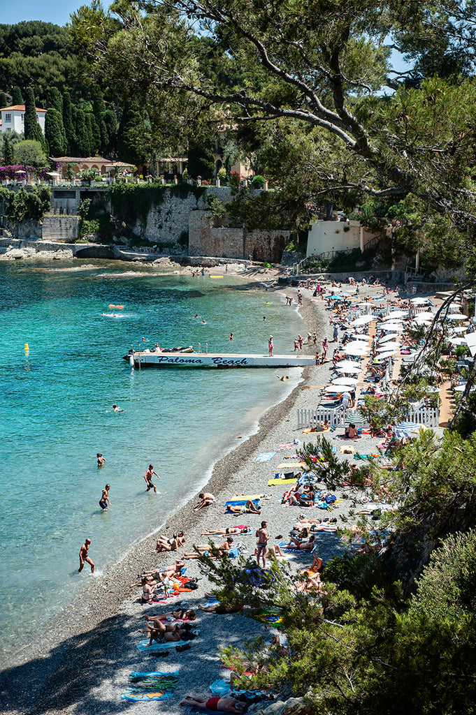 French Riviera wall art featuring Paloma Beach shot from above  on a busy hot summer day with beachgoers in the water and relaxing on the private Paloma beach and the public area by Photographer Millie Brown