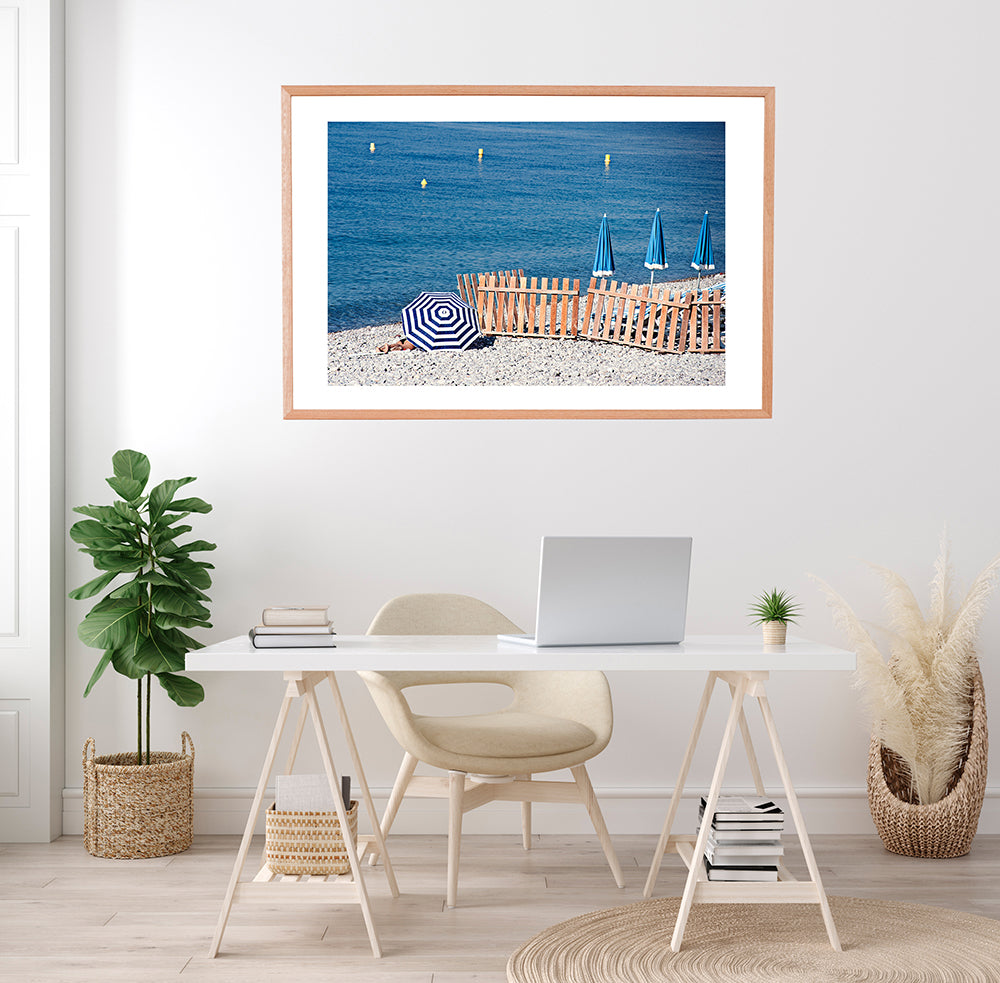 French Riviera Wall Art Print featuring the pebbly beach in Nice France and a blue and blue beach umbrellas next to the blue mediterranean sea