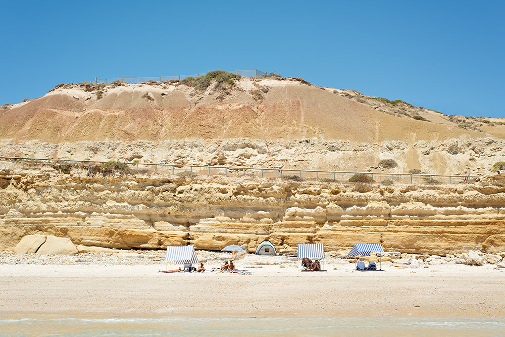 Australian Beach Art featuring Port willunga beach on the Fleurieu Peninsula South Australia , magnificent golden cliffs soar into a big blue sky with the white sand of the beach and clear ocean in the foreground and beachgoers under beach shades enjoying the summer sun. Fine art beach print by Millie Brown