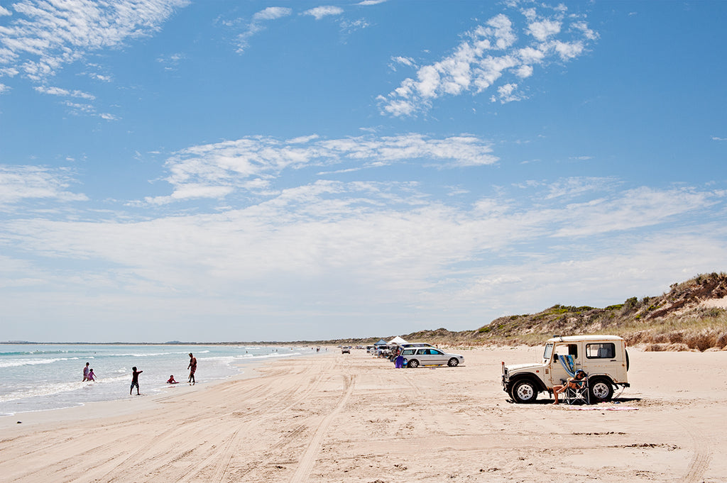 Summer day on Long Beach in Robe on the South Australian limestone coast. Featuring a land rover on the beach and beach goers playing on the sand and in the ocean. Fine art print by Millie Brown