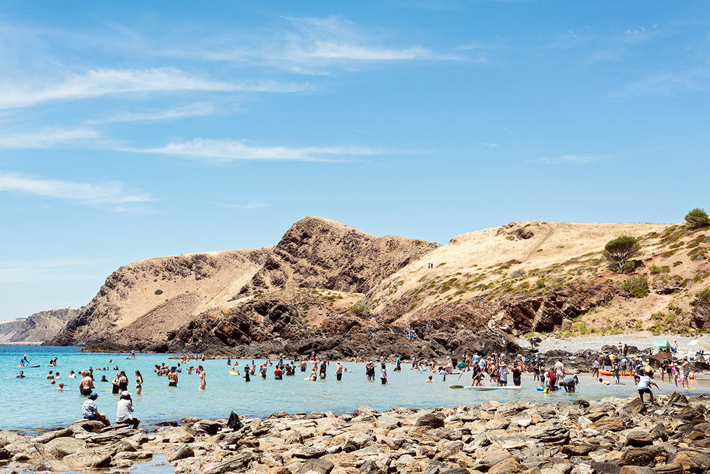 Second Valley Beach print on a hot summer day people swim, stand and kayak in the crystle blue water surrounded by the sunburned hills behind. Photographic print by professional photographer Millie Brown