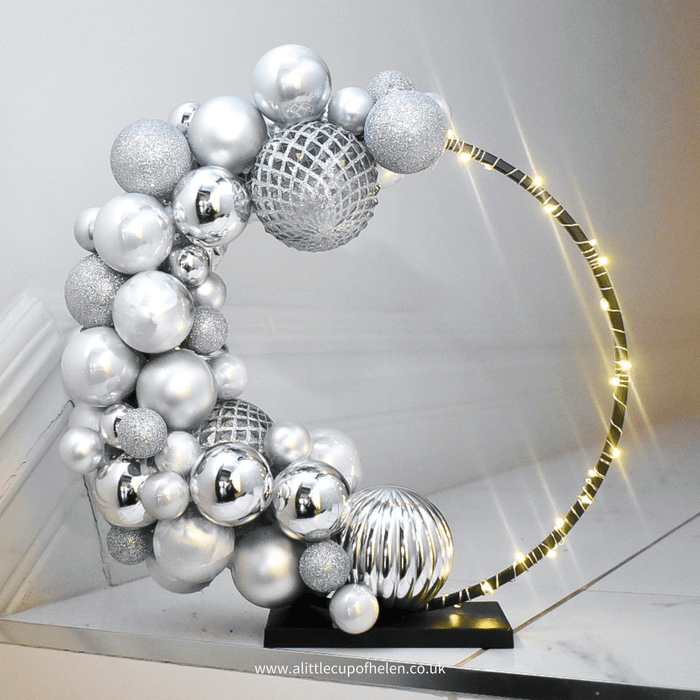 Oh Hello Christmas. A fabulous contemporary take on a Christmas centrepiece. A black standing hoop featuring a cocktail of delicious silver hues that can be appreciated from every angle.