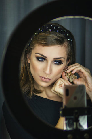 woman with smokey eye putting on earring in mirror