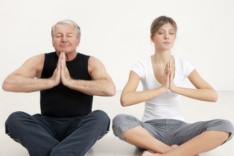 A man and a woman performing yoga.