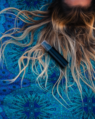 a person with blonde-brunette hair lying next to a sunscreen spray bottle