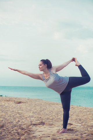 A woman performing yoga outdoors.