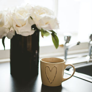 Beige Mug With Heart Full Of Sweet Love Coffee On Kitchen Counter With Flowers