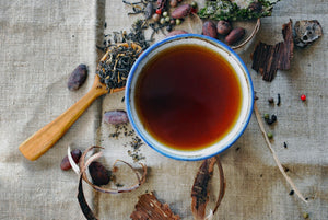 Blue Rimmed Cup Of Herbal Tea With Various Loose Tea Leaves And Nuts On Linen Cloth