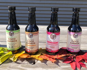 Four Bottles Of Big Tree Farms Organic Cooking Sauces Made With Coconut Aminos Sitting Outside On Autumn Leaves