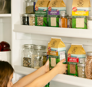 Child Reaching For Carton Of Light Brown Rice Golden Ralston Rice In Kitchen Pantry