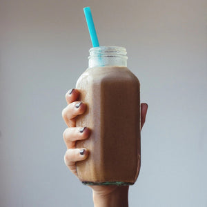 Hand Holding Glass Bottle Of Rich Organic Chocolate Smoothie
